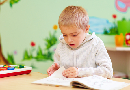 cute boy, kid with special needs looking at a book, in rehabilitation center Stockfoto