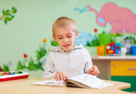 Menino bonito, garoto com necessidades especiais, olhando para um livro, no centro de reabilitação Foto de archivo - 68968912