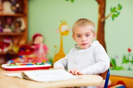 かわいい男の子、リハビリテーション センターでの学習の特別なニーズを持つ子供 写真素材