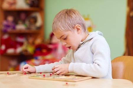 귀여운 소년, 재활 센터에서 퍼즐을 해결하는 특별한 도움이 필요한 아이