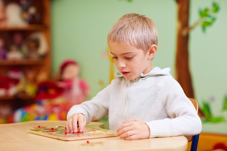 cute boy, kid with special needs solving a puzzle in rehabilitation center Standard-Bild