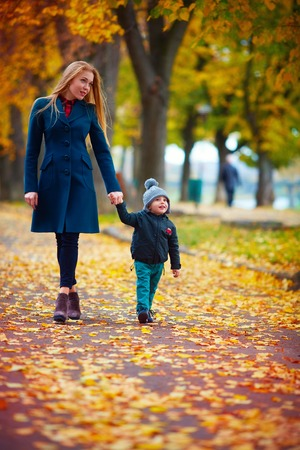 outer clothing: young mother with little son walking on autumn street