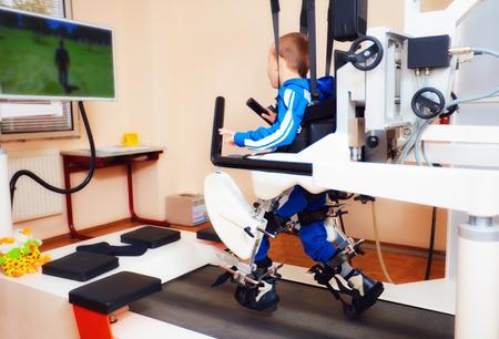 젊은 소년은 재활 센터에서 로봇 보행 치료를 통과합니다