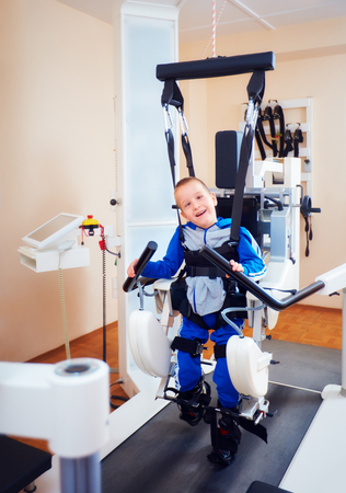 cords: young boy passes robotic gait therapy in rehabilitation center
