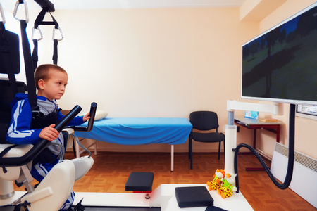 sclerosis: young boy passes robotic gait therapy in rehabilitation center