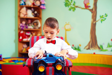 benevolence: cute happy kid on wheelchair with present in kindergarten for kids with special needs Stock Photo
