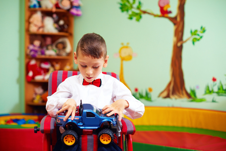 cute happy kid on wheelchair with present in kindergarten for kids with special needs Stock Photo