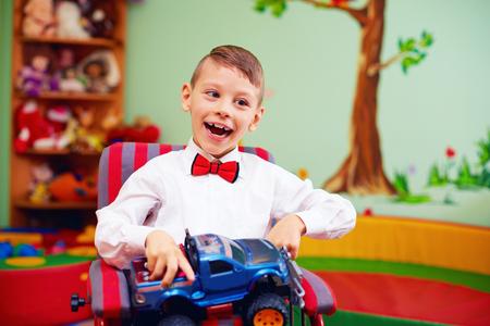 schattig gelukkig kind op rolstoel met heden in de kleuterschool voor kinderen met speciale behoeften Stockfoto