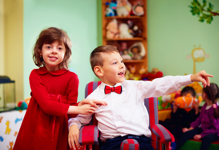 special needs: cute little gentleman in wheelchair and lady on holidays in kindergarten for kids with special needs