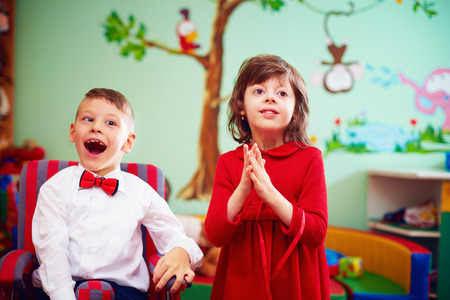 in anticipation of the holidays. cute gentleman in wheelchair and lady in rehabilitation center for kids with special needs Stock Photo