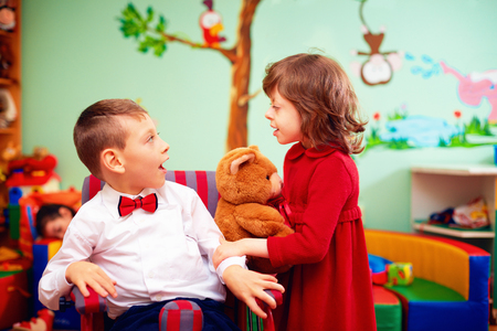 cerebral palsy: cute little gentleman in wheelchair and lady on holidays in kindergarten for kids with special needs