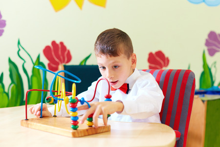 cerebral palsy: cute boy, kid in wheelchair solving logical puzzle in rehabilitation center for children with special needs Stock Photo