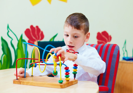 special needs: cute boy, kid in wheelchair solving logical puzzle in rehabilitation center for children with special needs Stock Photo