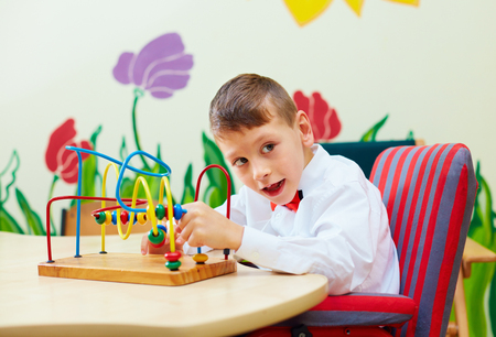 cute boy, kid in wheelchair solving logical puzzle in rehabilitation center for children with special needs Stockfoto