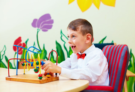 special education: cute boy, kid in wheelchair solving logical puzzle in rehabilitation center for children with special needs Stock Photo