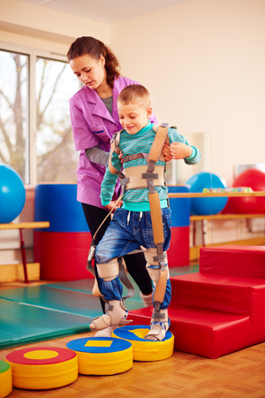 cerebral palsy: cute kid having physical musculoskeletal therapy in rehabilitation center Stock Photo
