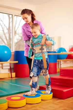 Simpatico ragazzo con la terapia fisica muscolo-scheletrico nel centro di riabilitazione Archivio Fotografico - 66132833