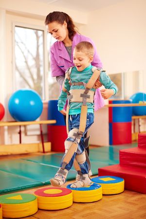cute kid having physical musculoskeletal therapy in rehabilitation center Foto de archivo
