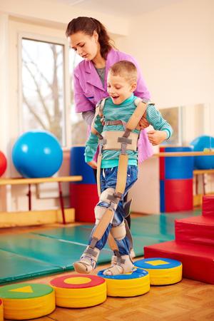 Simpatico ragazzo con la terapia fisica muscolo-scheletrico nel centro di riabilitazione Archivio Fotografico - 66019236