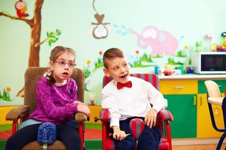 lindo de los niños en sillas de ruedas en el jardín de infantes para niños con necesidades especiales