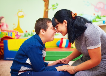 soulful moment. portrait of mother and her beloved son with disability in rehabilitation center Standard-Bild