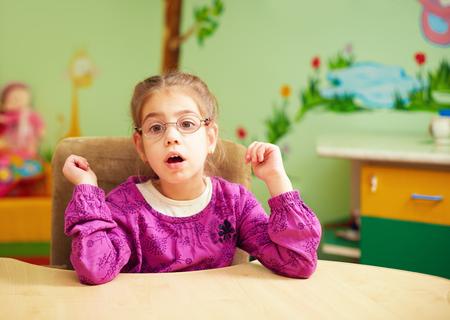 educacion fisica: niña linda en el jardín de infantes para los niños con necesidades especiales