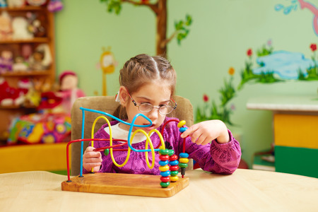 cute little girl playing with developing toy in kindergarten for kids with special needs Stockfoto