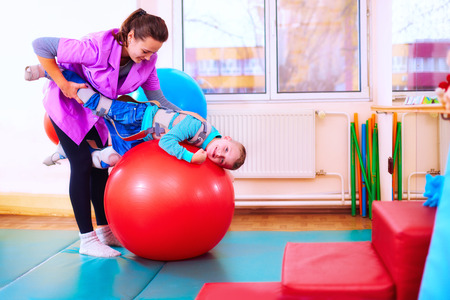 cute kid with disability has musculoskeletal therapy by doing exercises in body fixing belts on fit ball Stock Photo - 66254891