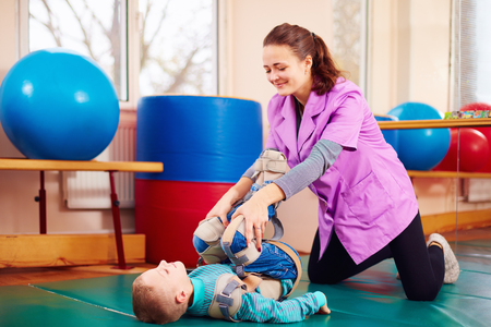 cute kid with disability has musculoskeletal therapy by doing exercises in body fixing belts Archivio Fotografico