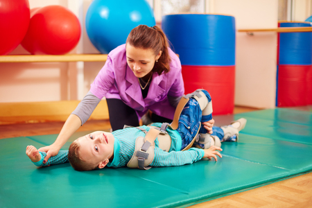 cute kid with disability has musculoskeletal therapy by doing exercises in body fixing belts Foto de archivo