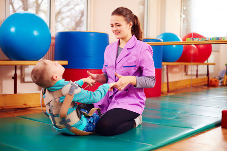 장애가있는 귀여운 아이가 신체 고정 벨트에서 운동을함으로써 근골격 치료를받습니다.