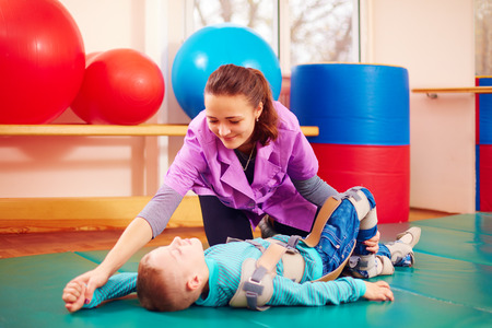 bends: cute kid with disability has musculoskeletal therapy by doing exercises in body fixing belts Stock Photo