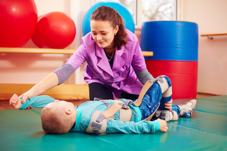 cute kid with disability has musculoskeletal therapy by doing exercises in body fixing belts Stockfoto
