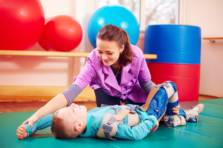 cute kid with disability has musculoskeletal therapy by doing exercises in body fixing belts Standard-Bild
