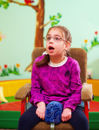 cerebral palsy: cute girl in wheelchair in kindergarten for children with special needs Stock Photo