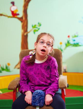 special needs: cute girl in wheelchair in kindergarten for children with special needs Stock Photo