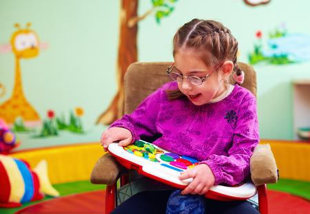 유치원에서 특별한 요구가있는 어린이를위한 장난감을 개발하면서 놀고있는 휠체어에 귀여운 소녀