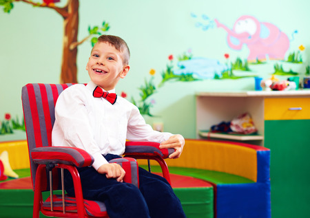 cute happy kid in wheelchair, wearing glad rags in center for children with special needs