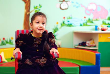 특별한 도움이 필요한 아이들을위한 재활 센터의 휠체어에있는 귀여운 소녀 스톡 콘텐츠