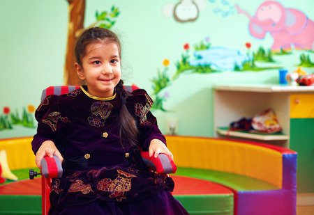 autistic: cute little girl in wheelchair at rehabilitation center for kids with special needs