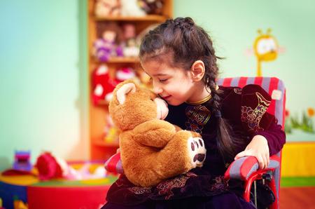그녀의 비밀을 말하고있는 휠체어의 귀여운 어린 소녀가 특별한 필요를 가진 아이들을위한 유치원에서 곰을 봉제한다.