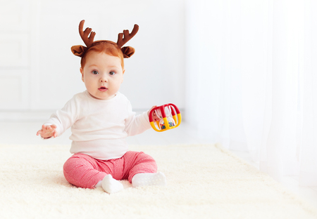 beautiful baby dear playing with toy at home Stock Photo