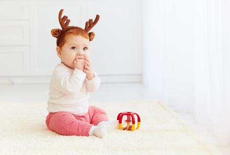 bebe sentado: hermosa querida bebé que juega con el juguete en el hogar