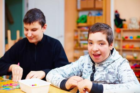 障害者の幸せな子供が特別なニーズを持つ子供のためリハビリテーション センターで彼らの良い運動能力を開発します。 写真素材
