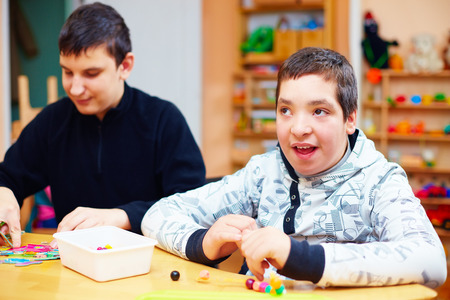 happy kids with disability develop their fine motor skills at rehabilitation center for kids with special needs Stock Photo