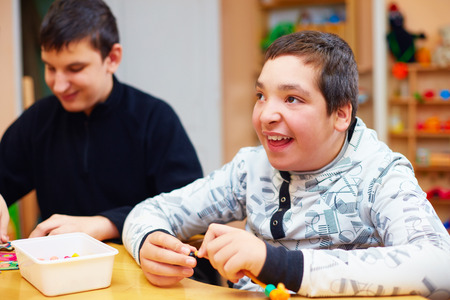 cerebral palsy: happy kids with disability develop their fine motor skills at rehabilitation center for kids with special needs Stock Photo