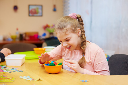 cerebral palsy: cute happy girl with disability develops the fine motor skills at rehabilitation center for kids with special needs