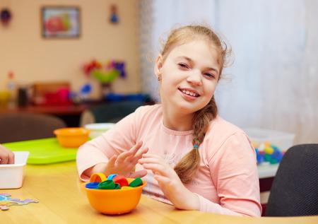 장애가있는 귀여운 행복한 소녀가 특별한 필요를 가진 어린이를위한 재활 센터에서 훌륭한 운동 기술을 개발합니다. 스톡 콘텐츠