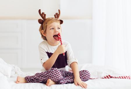 冬の朝のクリスマスのお菓子を舐めているかわいい子供
