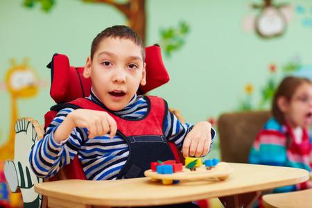 특별한 도움이 필요한 어린이를위한 재활 센터에서 장애를 가진 쾌활한 소년 스톡 콘텐츠